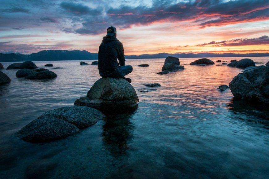 Modern Mystery School man on rock on sea shore